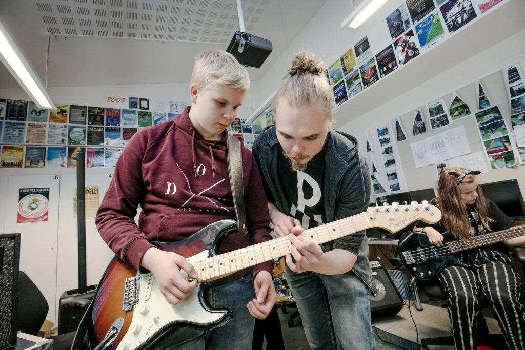 Bändileiriläinen saa kitaransoiton opetusta.