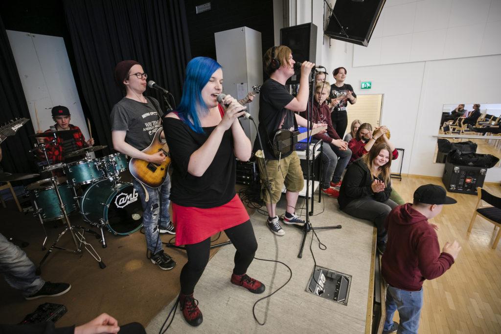 Bändileiri, lavalla yhtye esiintymässä, lavan reunalla leiriläisiä.
