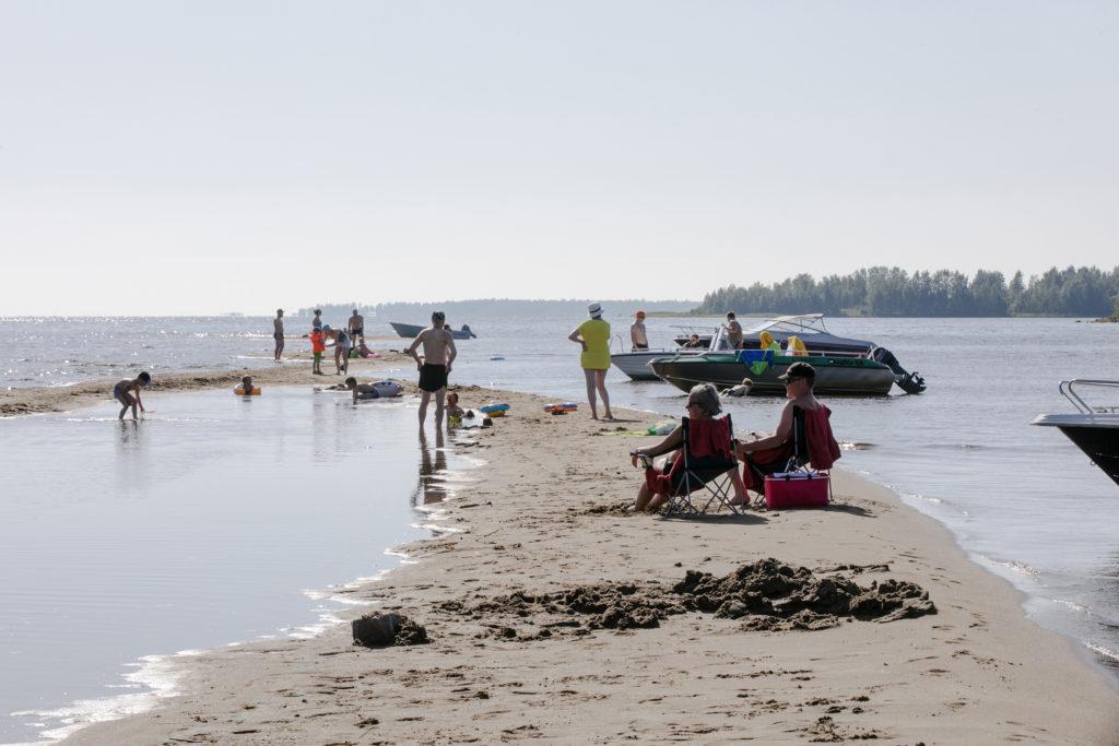 Ihmisiä meren rannalla viettämässä hellepäivää.
