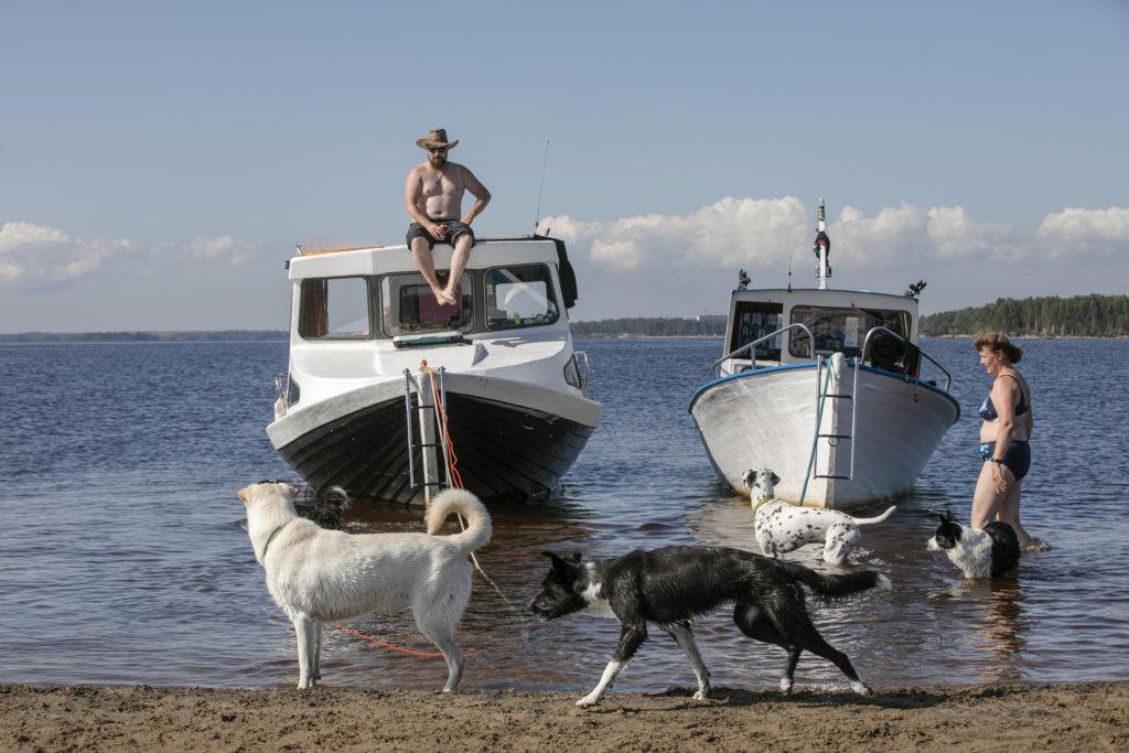 Hiekkarannan kupeessa kaksi venettä vedessä, neljä koiraa ja kaksi ihmistä.