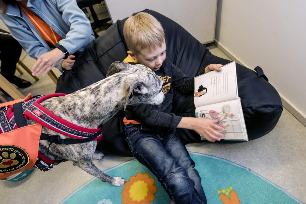 Kemin kaupunginkirjasto. Niilo Ylinen lukee kirjaa säkkituolissa. Vierellä Max-koira kuuntelee.