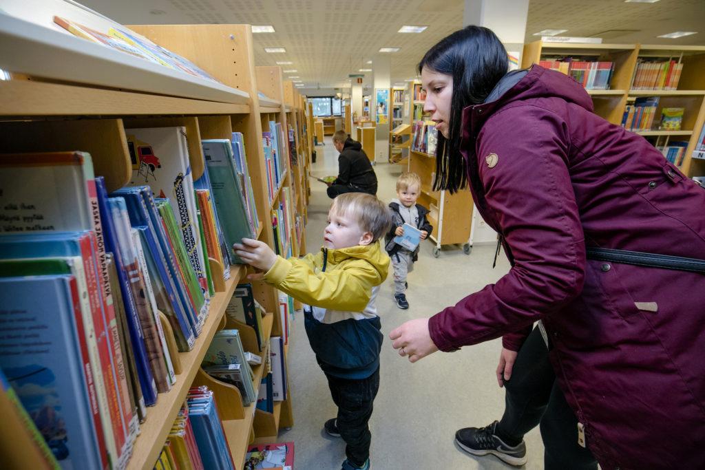 Aksila-Kaupin perhe kirjastossa. Etualalla Väinö Aksila ja Suvi Kauppi, taustalla Mika ja Leo Aksila.
