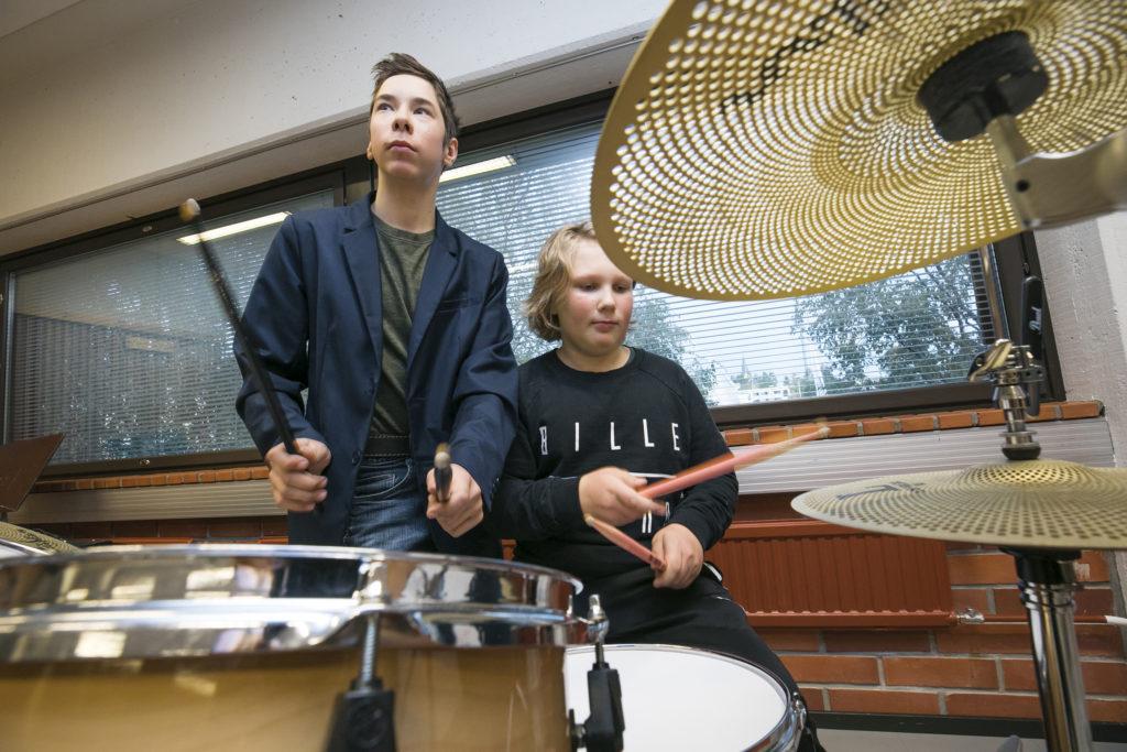Kaksi poikaa rumputunnilla musiikkiopistossa.