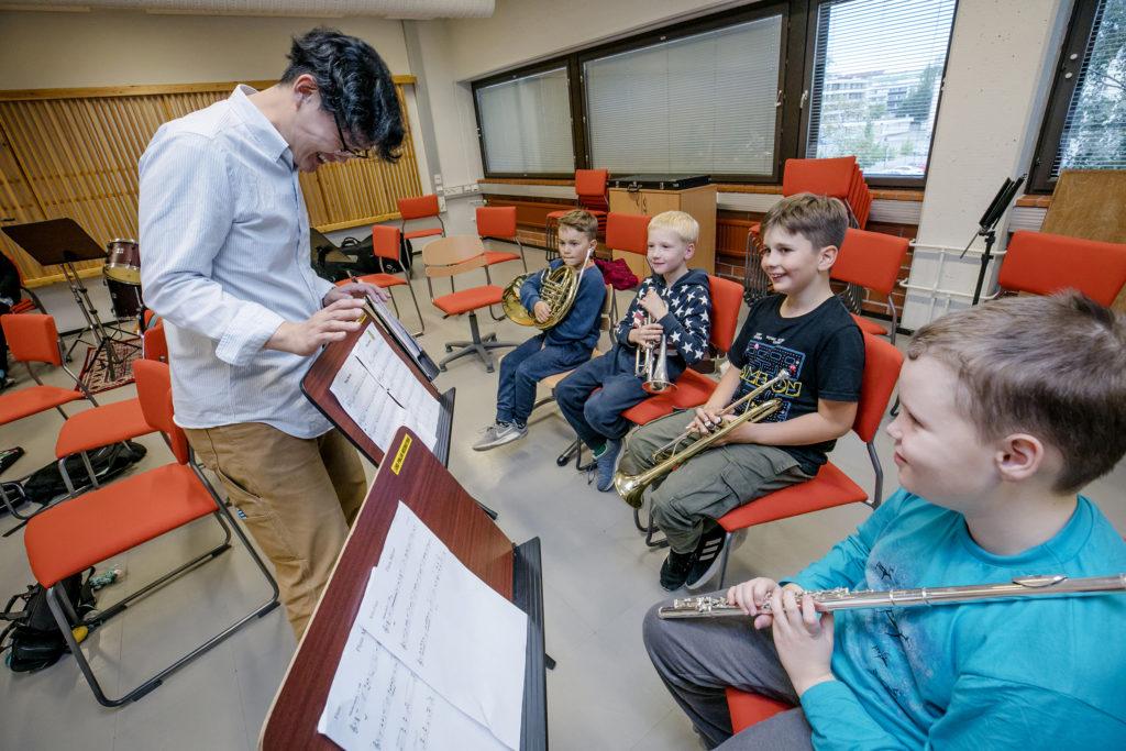 Neljä poikaa puhallintunnilla musiikkiopistossa.