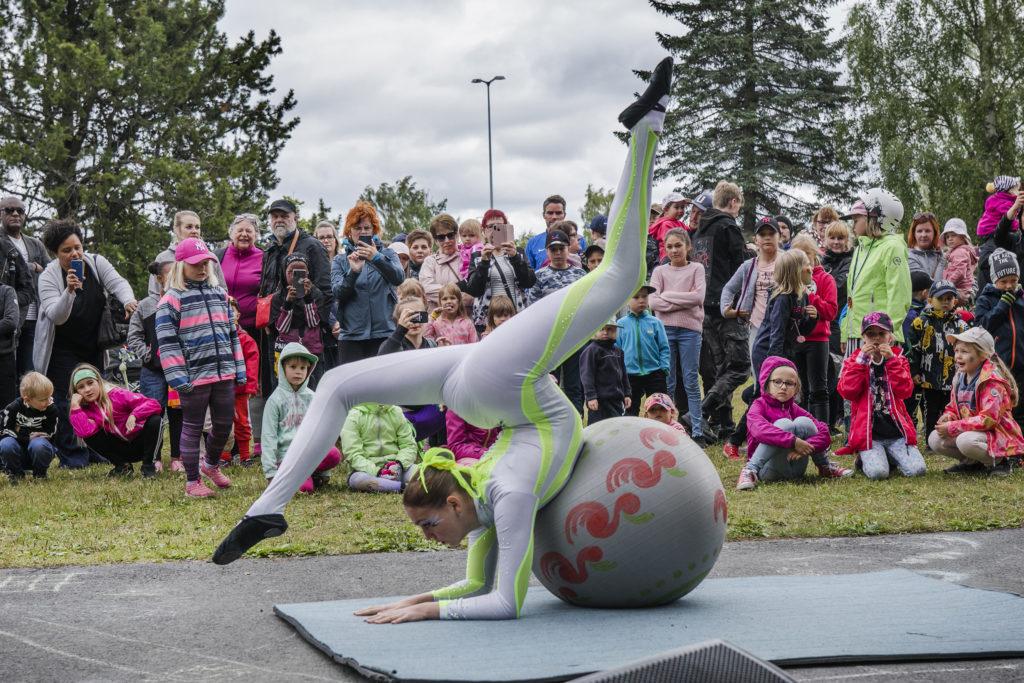 Lastentapahtumassa akrobaatti esiintyy puistossa, taustalla yleisöä.