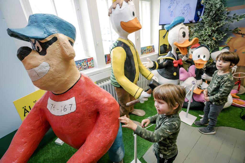 Kaksi pikkupoikaa sarjakuvakeskuksessa Aku Ankka -hahmoja ihmettelemässä.