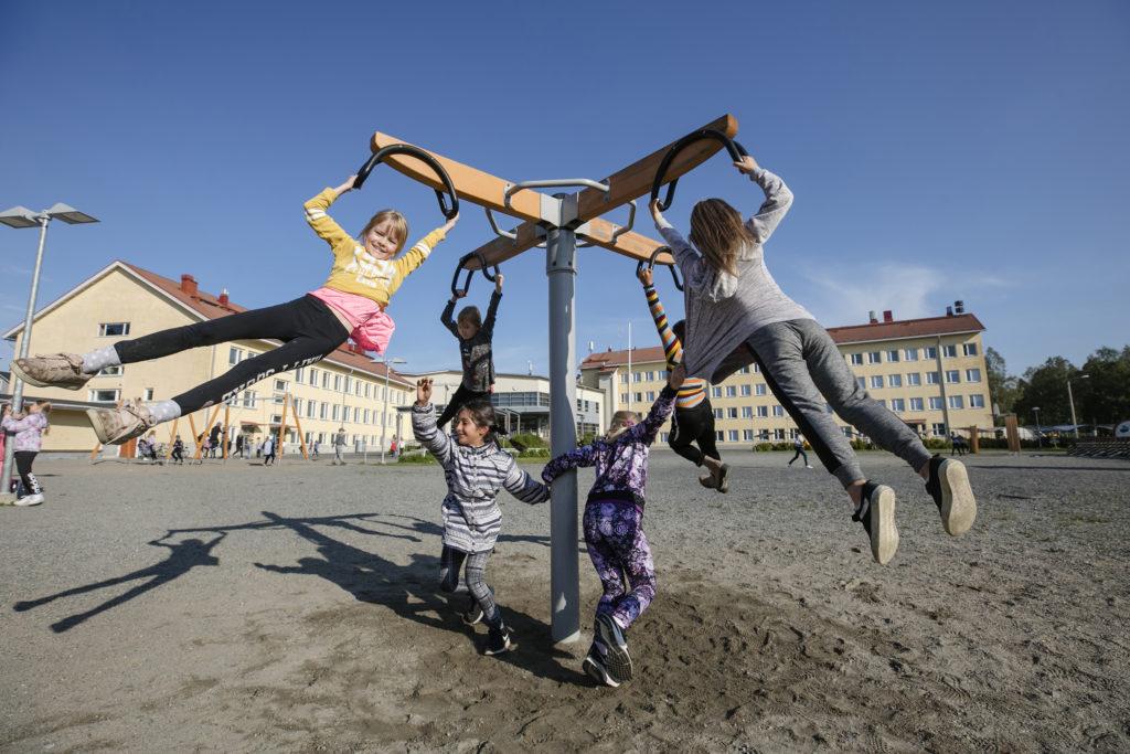 Kolmosluokkalaisia tyttöjä koulun pihan karusellissa.