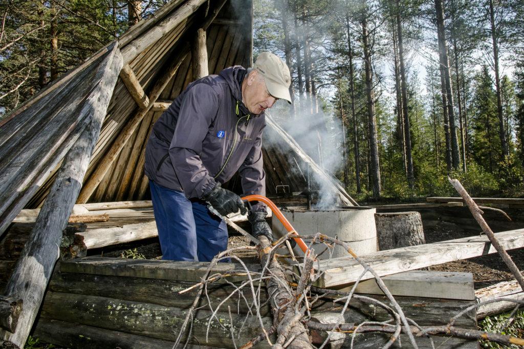 Mies sahaa polttopuuta laavulla.