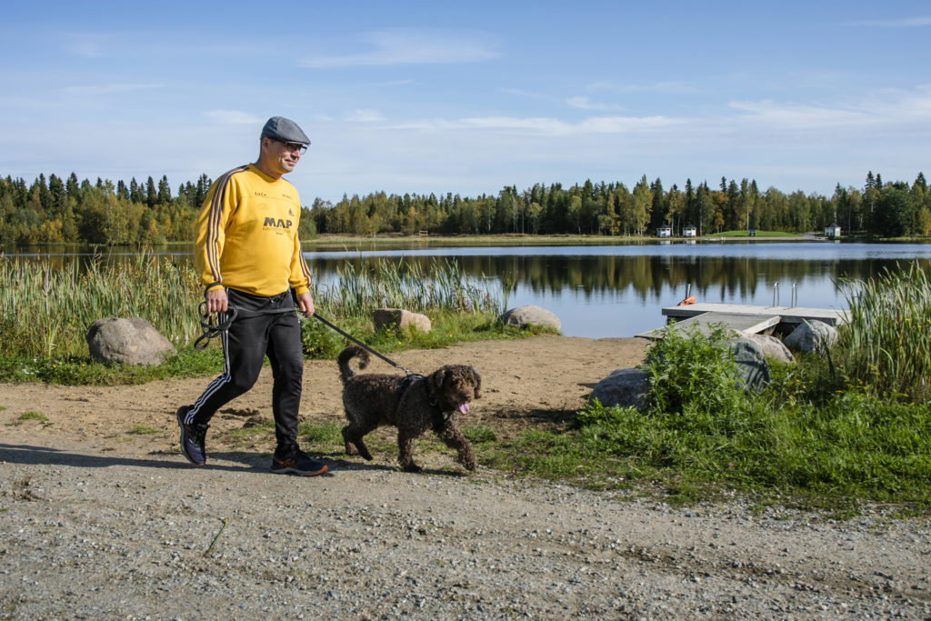 Mies koiran kanssa kävelylenkillä järven rannalla.