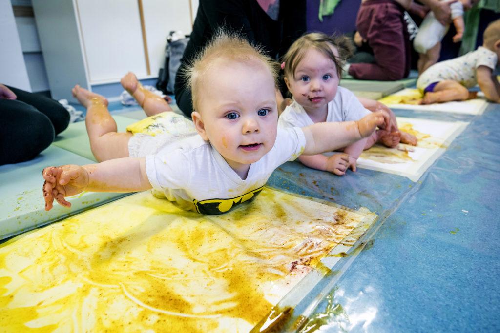 Bebisar som leker på golvet. Vauvoja värikylpyleikissä lattialla.