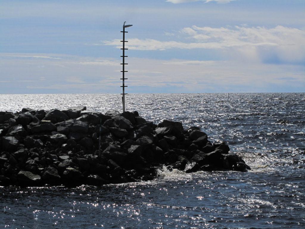 Aava meri, etualalla aallonmurtajan kiviröykkiöitä.