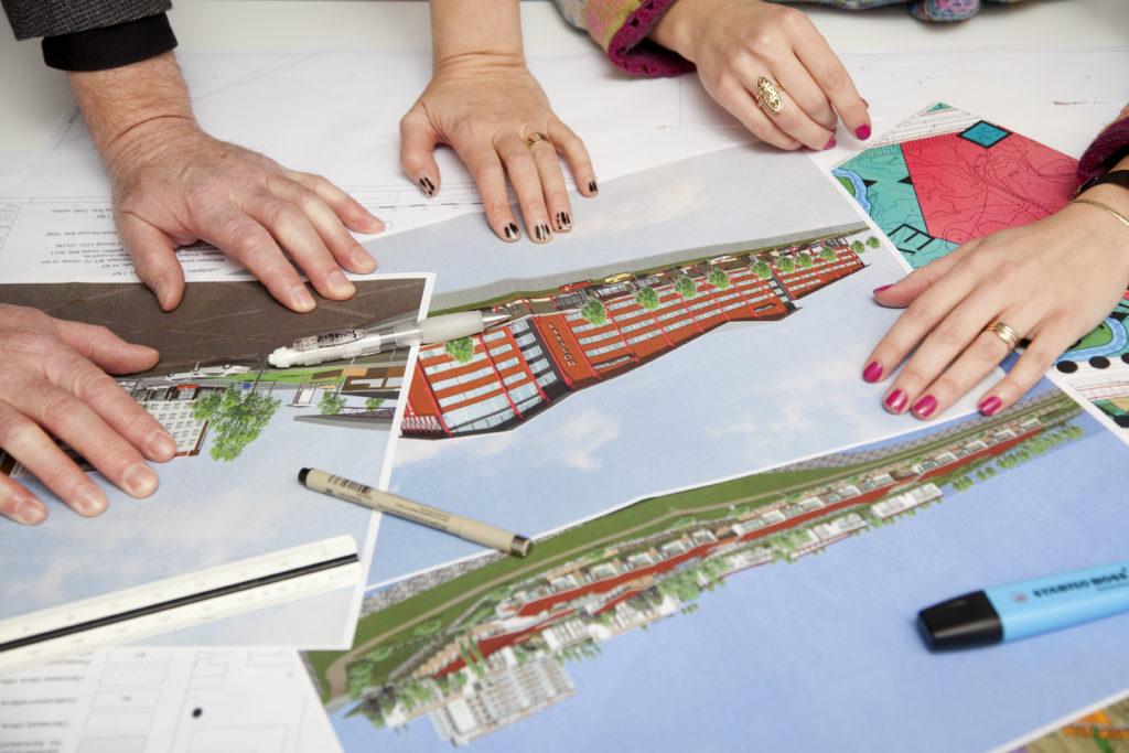 Rakennusten havainnepiirroksia pöydällä.