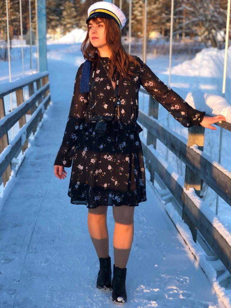 Nuori nainen lumisella puusillalla, valmistujaiskuva.