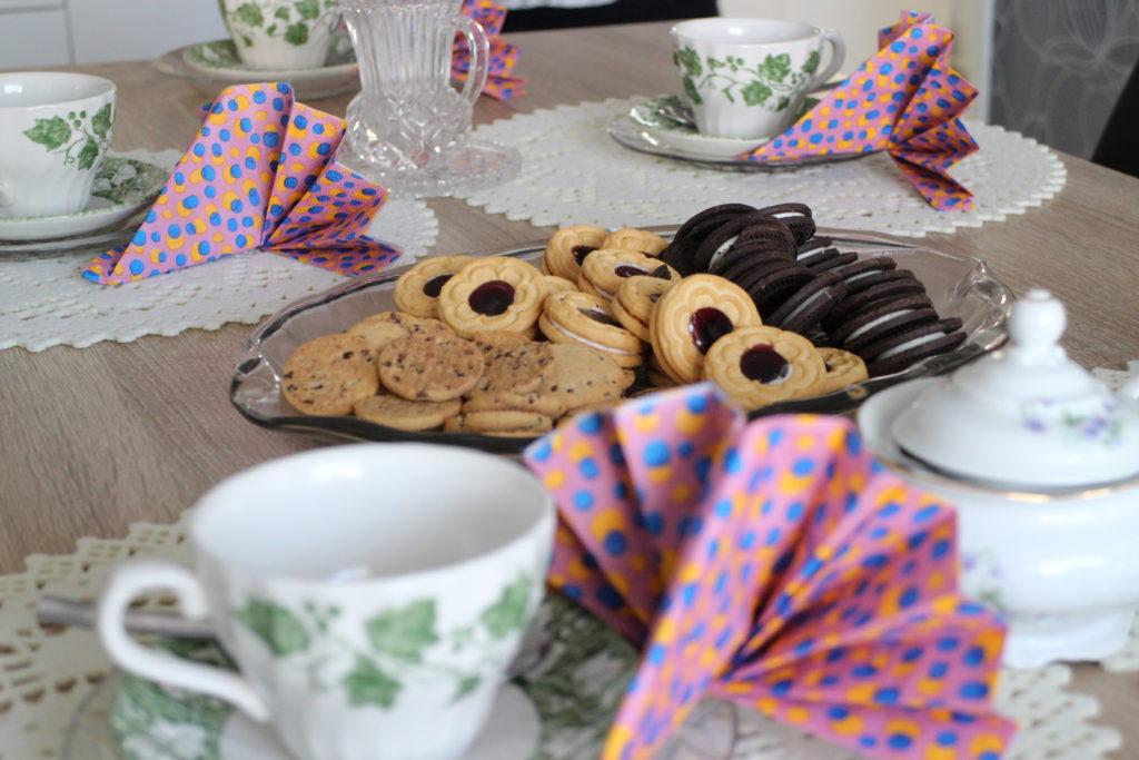 Lähikuva kahvipöydästä, keksejä lautasella, kahvikuppeja.