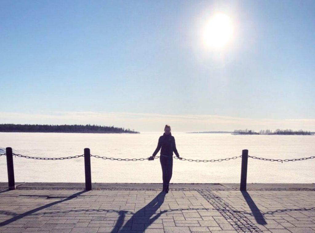 Nainen nojailee kaiteeseen meren rannalla. Talvikuva.