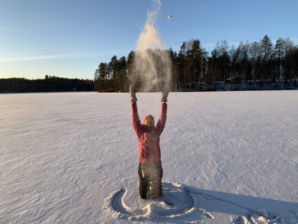 Nainen hangella heittelemässä lunta.