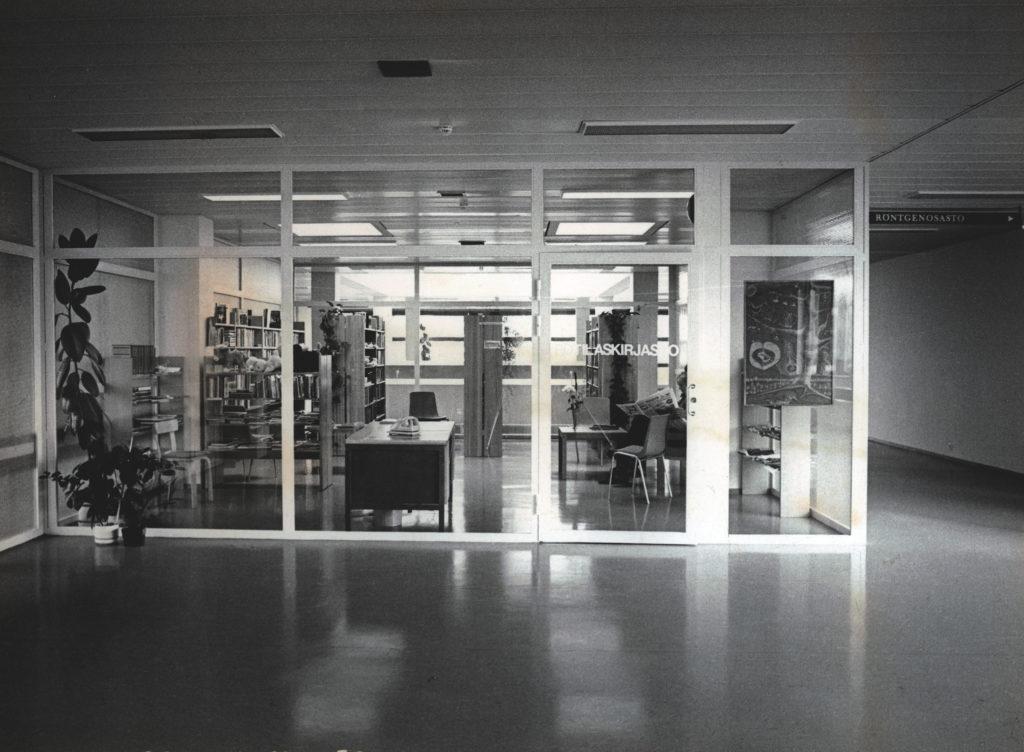 Kuva aulasta, jossa lasiseinän takana potilaskirjasto.