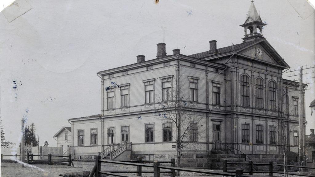 Vanha kaksikerroksinen puurakennus, vanha mustavalkoinen kuva.