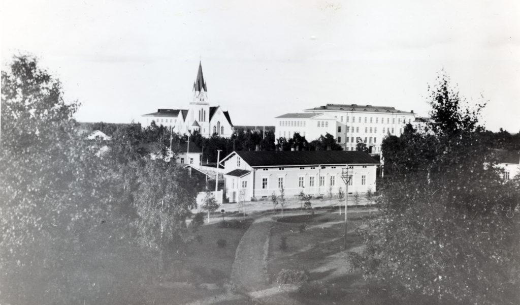 Vanha mustavalkoinen kuva Kemin keskustasta, etualalla puiston takana kaksikerroksinen puutalo, takana kirkko.