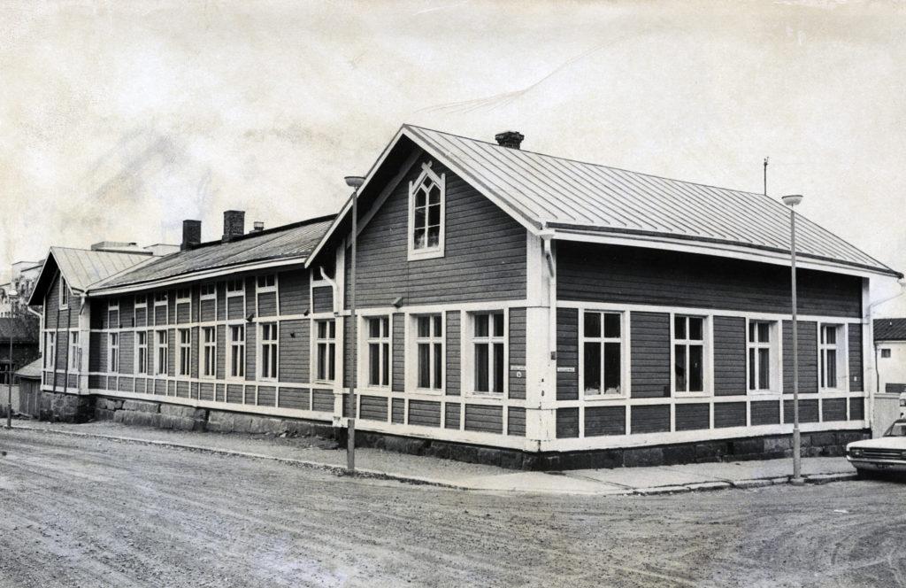 Mustavalkoinen kuva kadunkulmauksesta, jossa vanha puutalo.