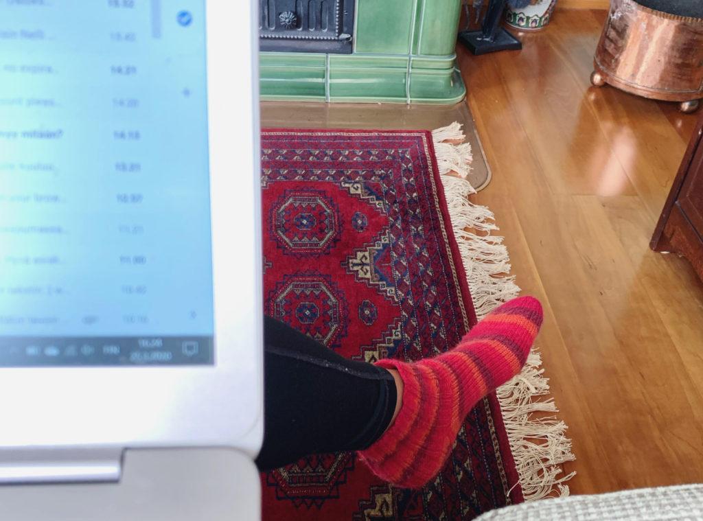 Ihminen työskentelee etänä tietokoneellaan omassa takkahuoneessaan.