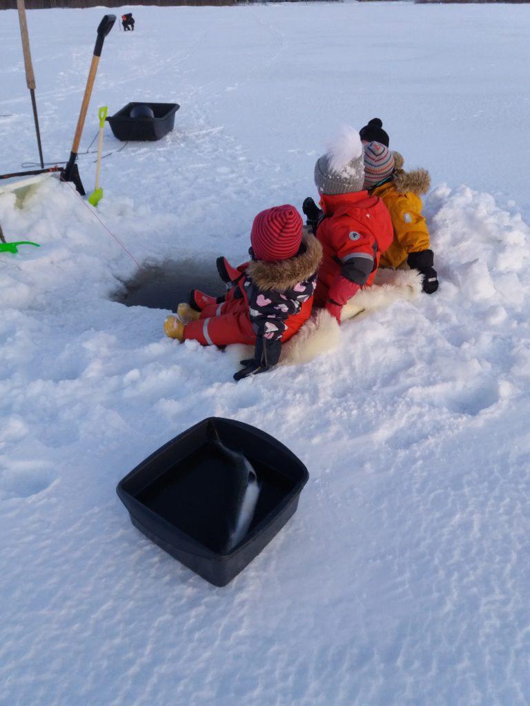 Lapsia istuu avannon vierellä jäällä.
