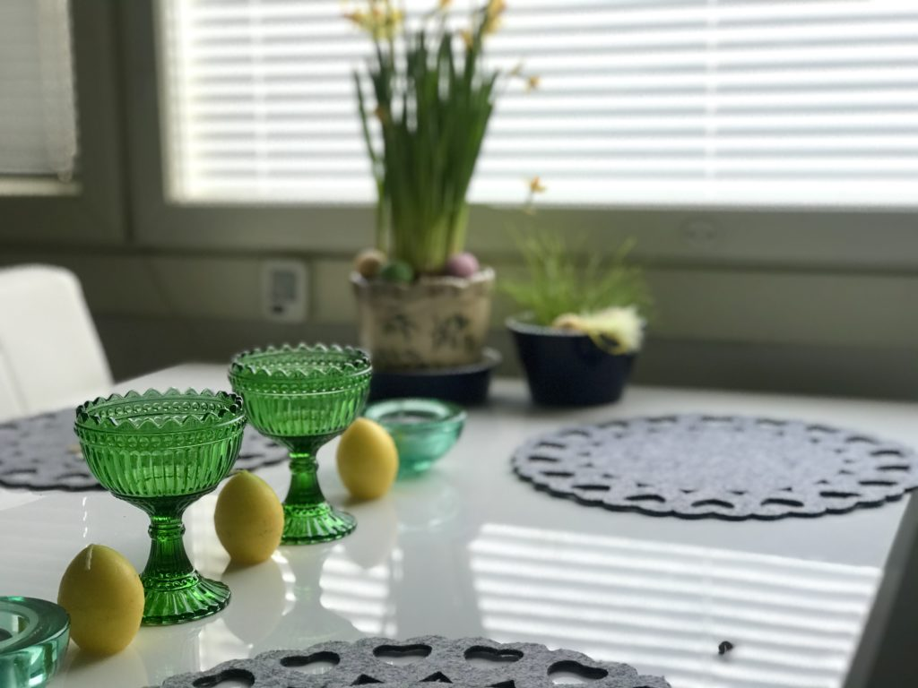 Pääsiäispöytä koristeltu mariskooleilla ja munilla, taustalla narsissiruukku.