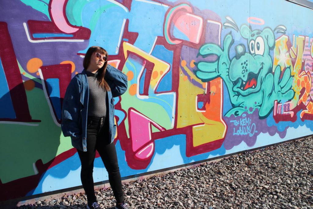 Nuori nainen seisoo värikkään seinägraffitin edustalla.
