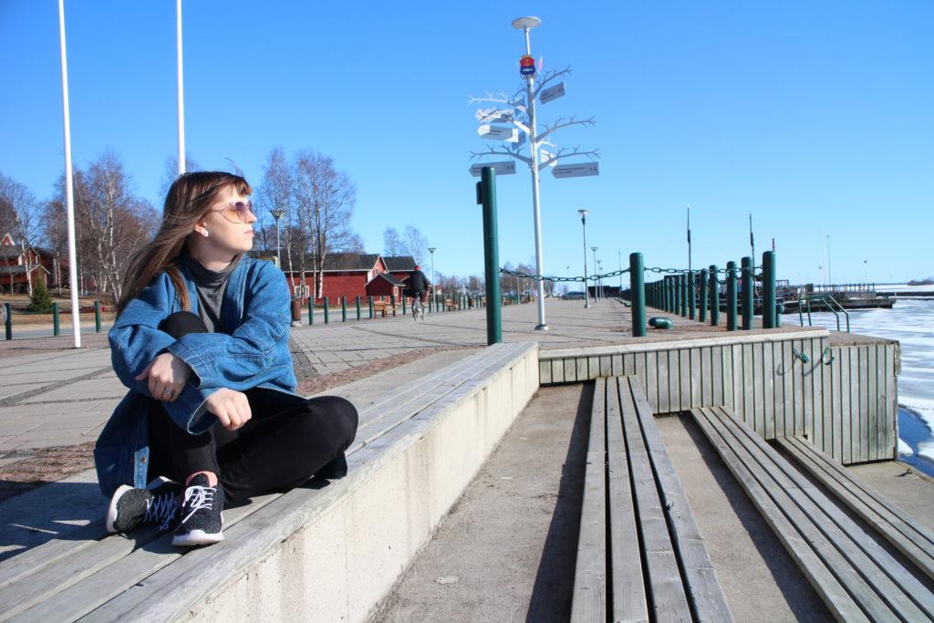 Nuori nainen istuu sisäsatamassa meriportailla.