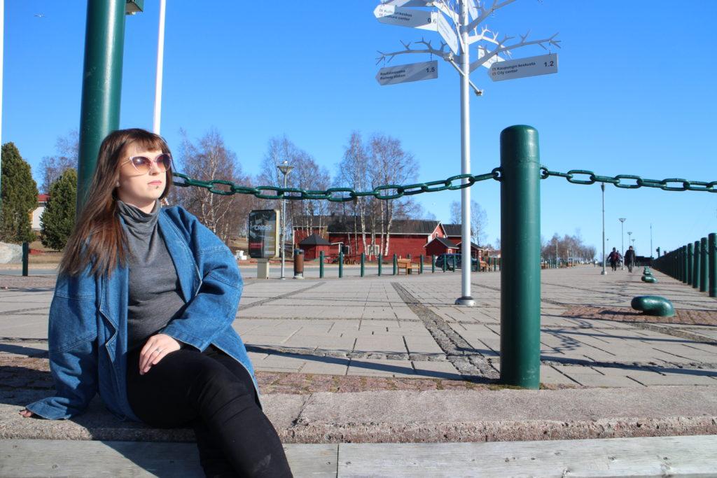 Nuori nainen istuu sisäsatamassa laiturin reunalla.