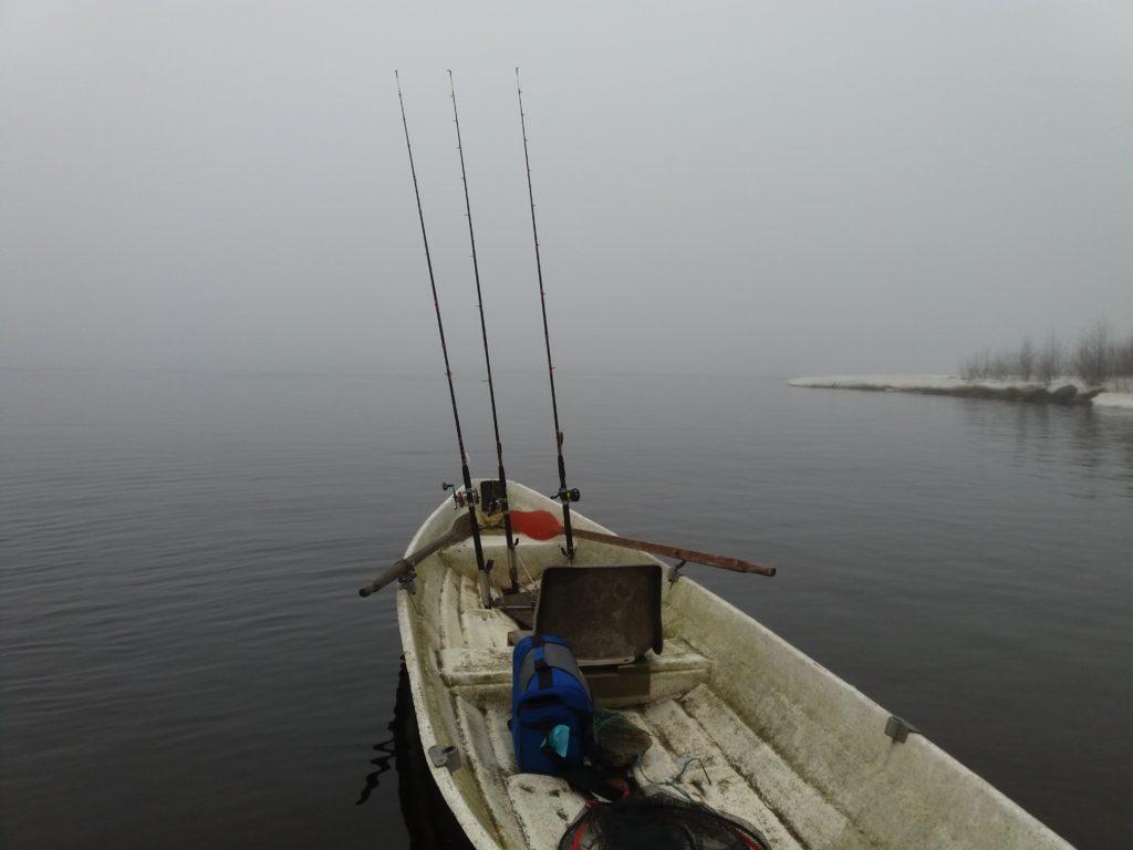 Sumuinen merimaisema. Etualalla vene, jossa kiinnitettynä kalastusvapoja.
