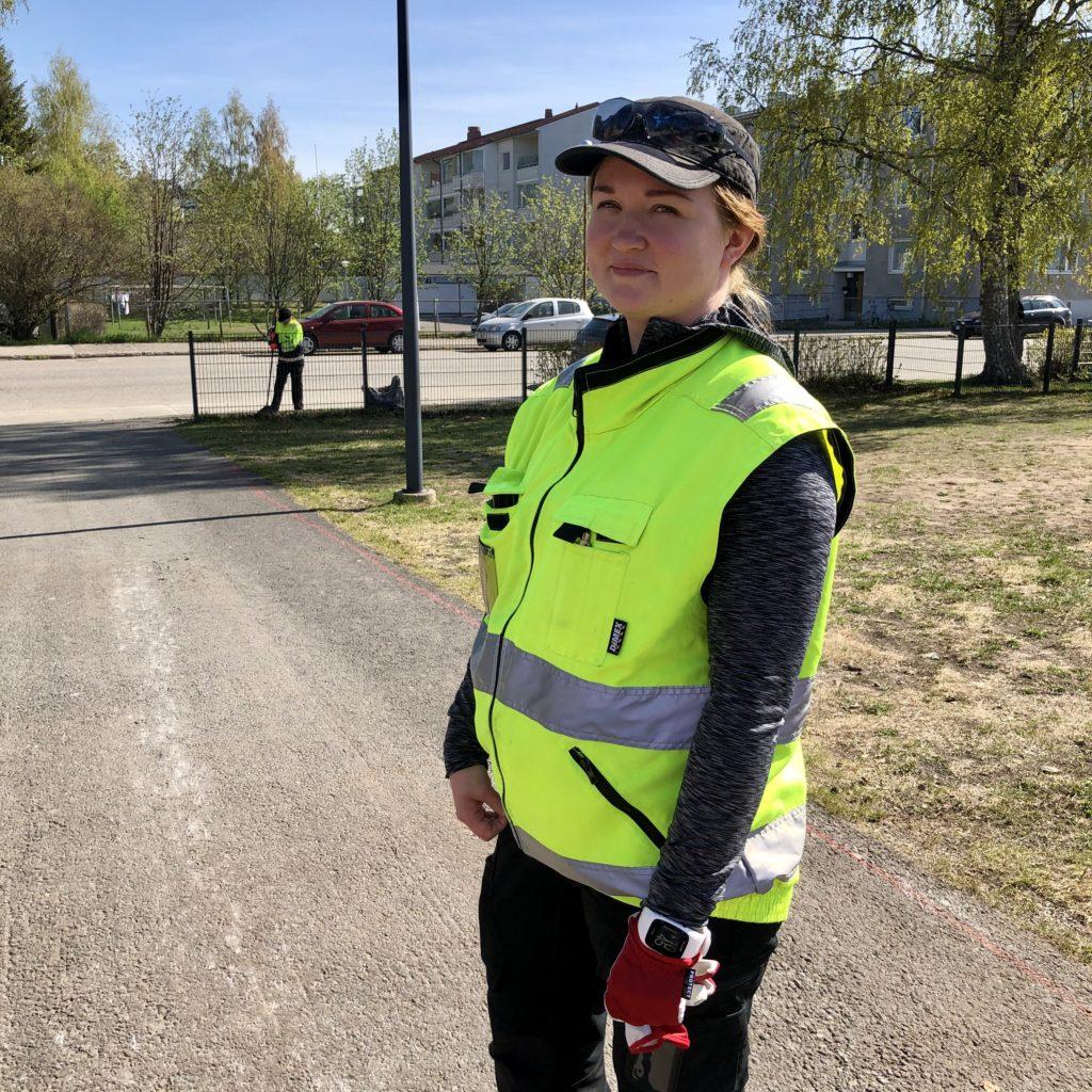 Kesätyönohjaaja, puutarhuri Hannele Leppänen Sauvosaaren koulun pihalla. Keltainen huomioliivi päällä.