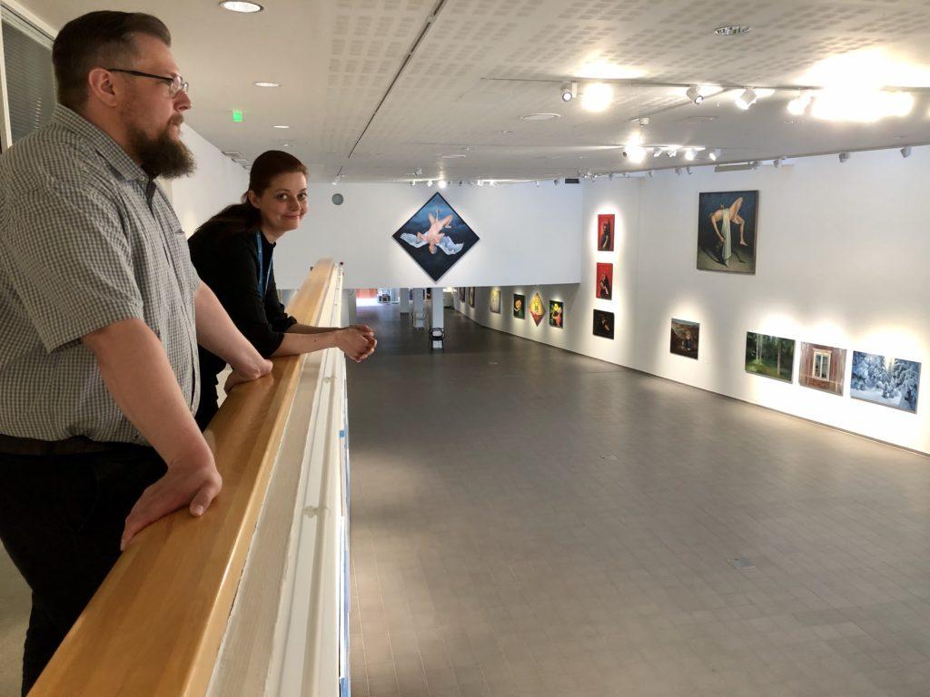 Janne Kuoppala ja Tanja Kavasvuo taidemuseon parvekkeella. Taustalla näyttelysali ja tauluja.