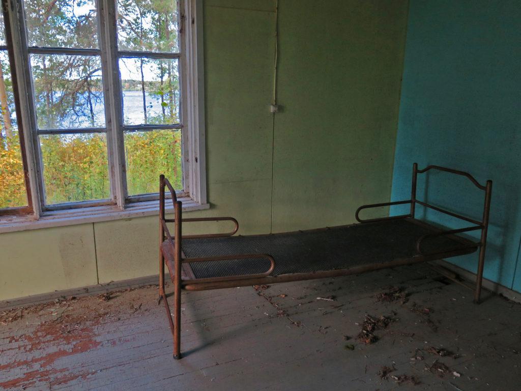 Vanha hetekasänky vanhan puutalon huoneessa.