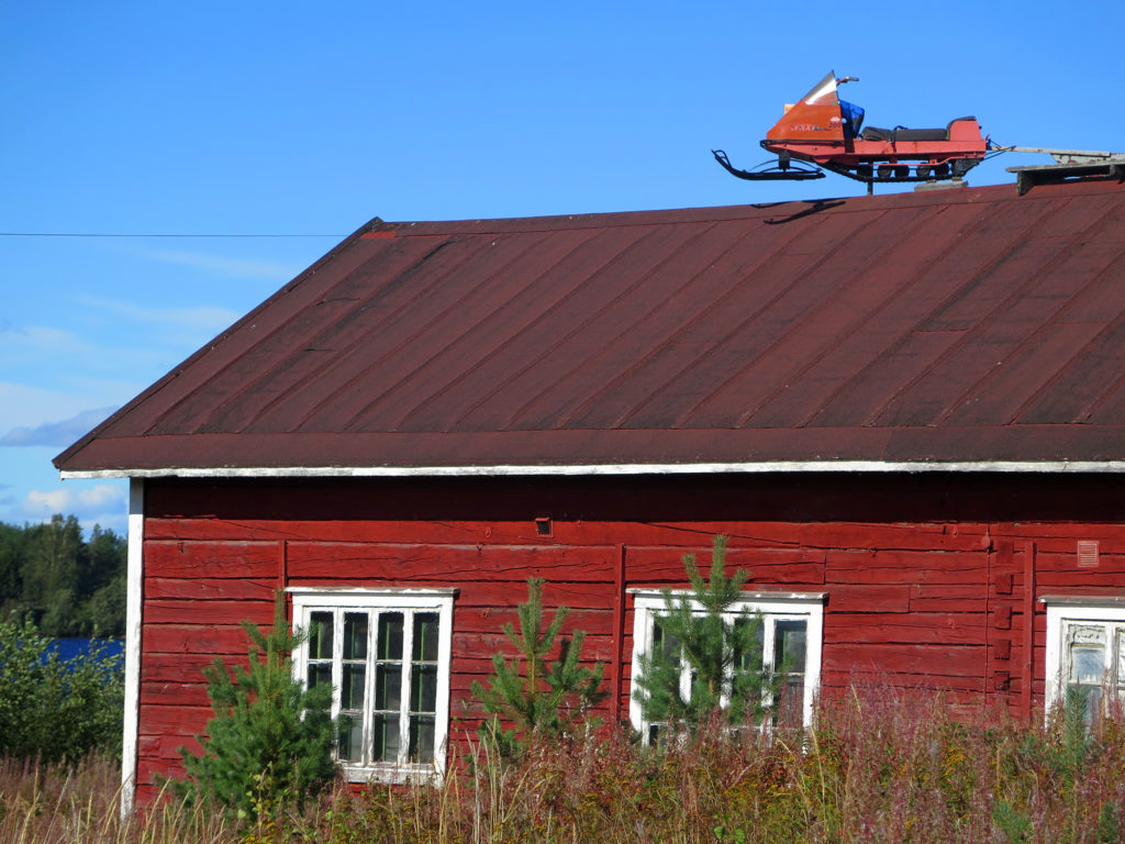 Punainen vanha hirsitalo, jonka katolla on moottorikelkka.