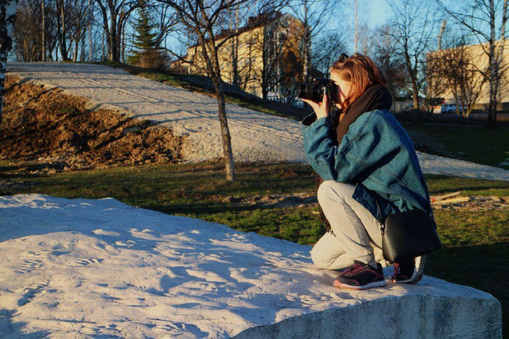 Nuori nainen kyykyssä sotalapsipatsaan reunalla valokuvaamassa