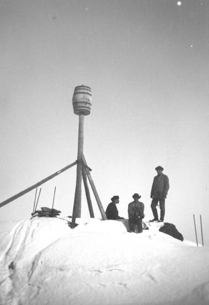 Vanha mustavalkokuva Kivaloiden vaarojen huipulta, kolme miestä lumessa.