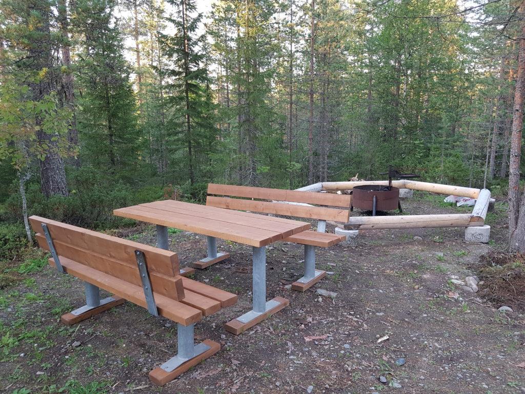 Tulistelupaikka metsässä, vierellä pöytä ja penkit.