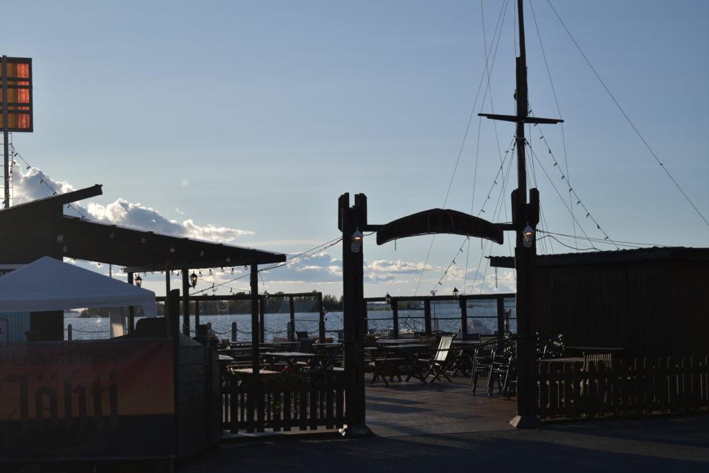 Sisäsataman terassiravintola etualalla, taustalla meri.