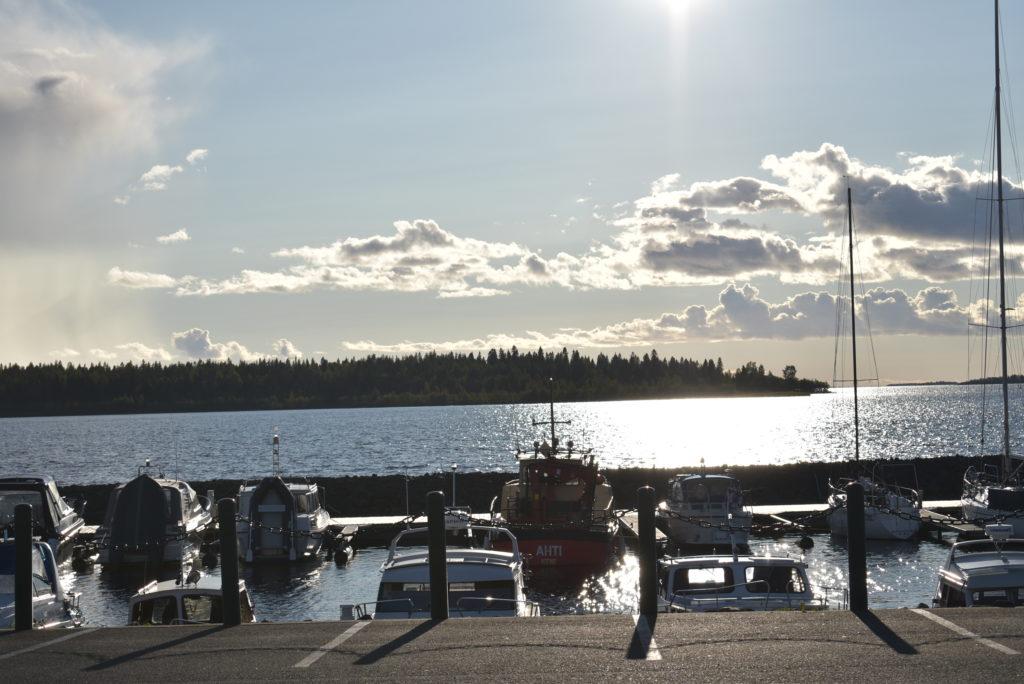 Pienvenesatama ja veneitä etualalla, taustalla meri.