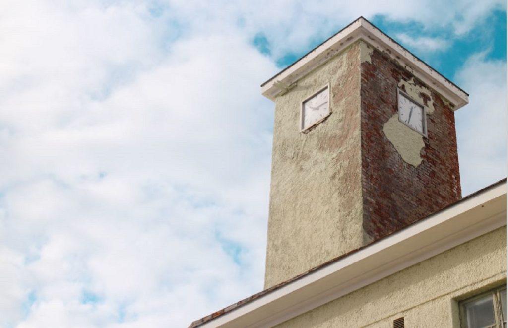 Tehdasrakennuksen ja tornin kellot lähikuvassa.