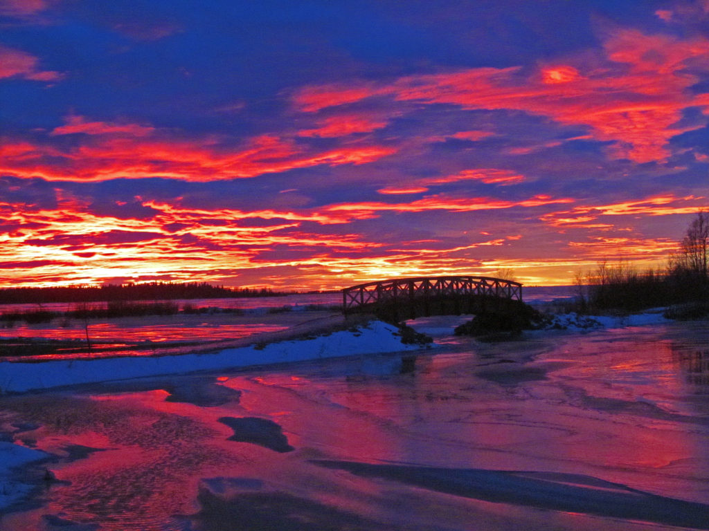 Puusilta merenlahdella, talvinen auringonlasku.