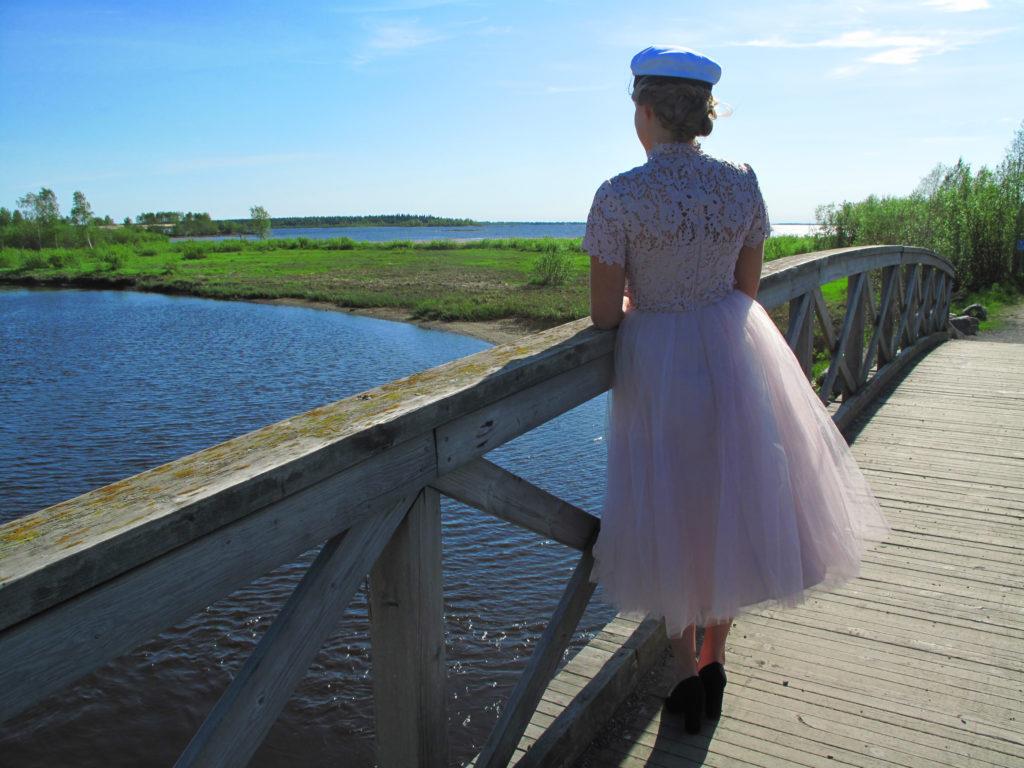 Nuori nainen ylioppilasasussa puusillalla merenrannalla.
