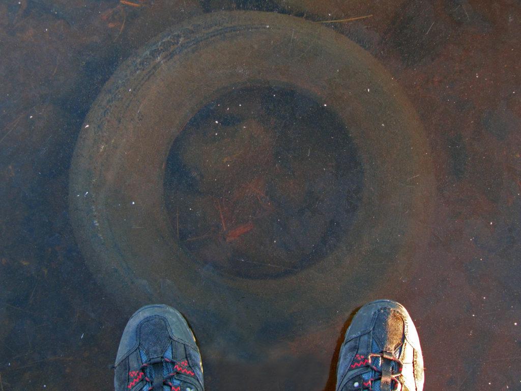 Vanha autonrengas matalassa vedessä.
