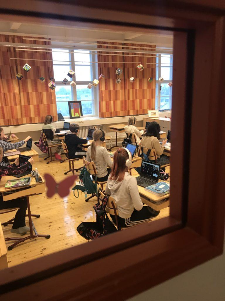 Oppilaita koululuokassa. Kuvattu ikkunan takaa.