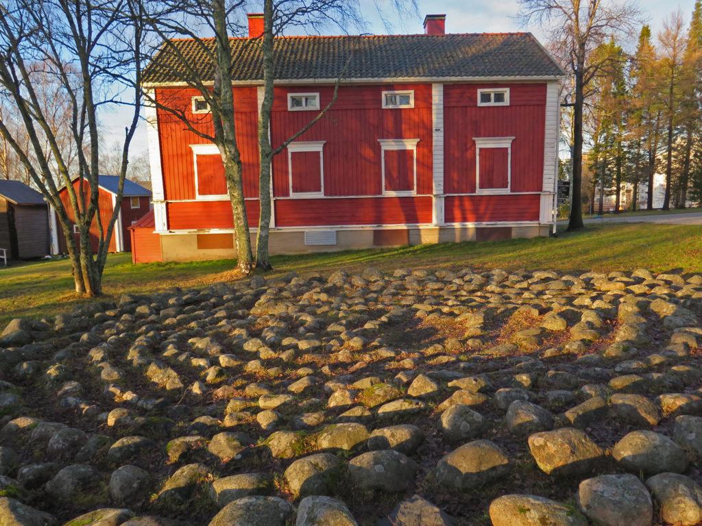 Vanha punainen rakennus jonka edessä jatulintarha