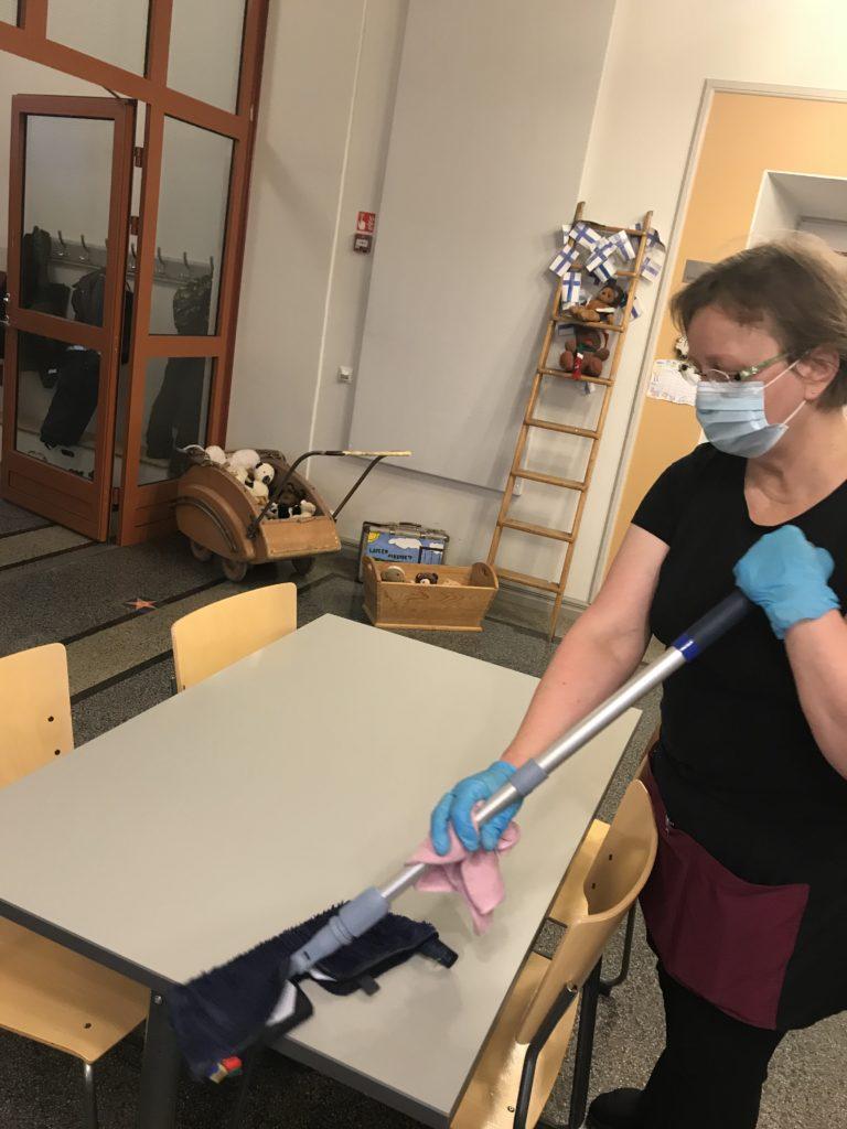 Siivooja puhdistamassa ruokapöytää koulussa.