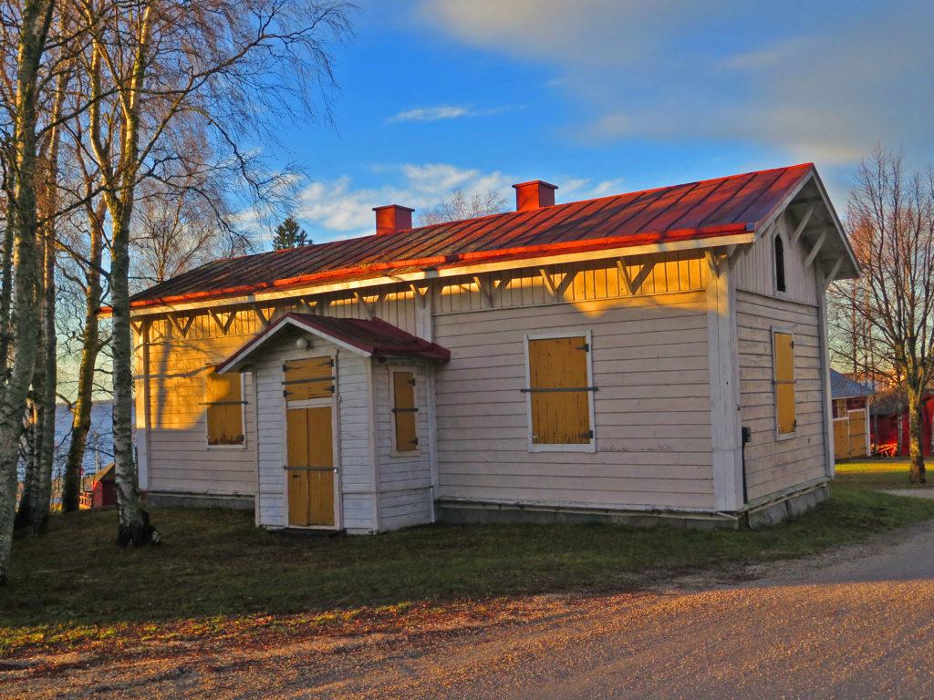 Vanha valkoinen puurakennus jonka ikkunoissa ja ovessa laudat edessä