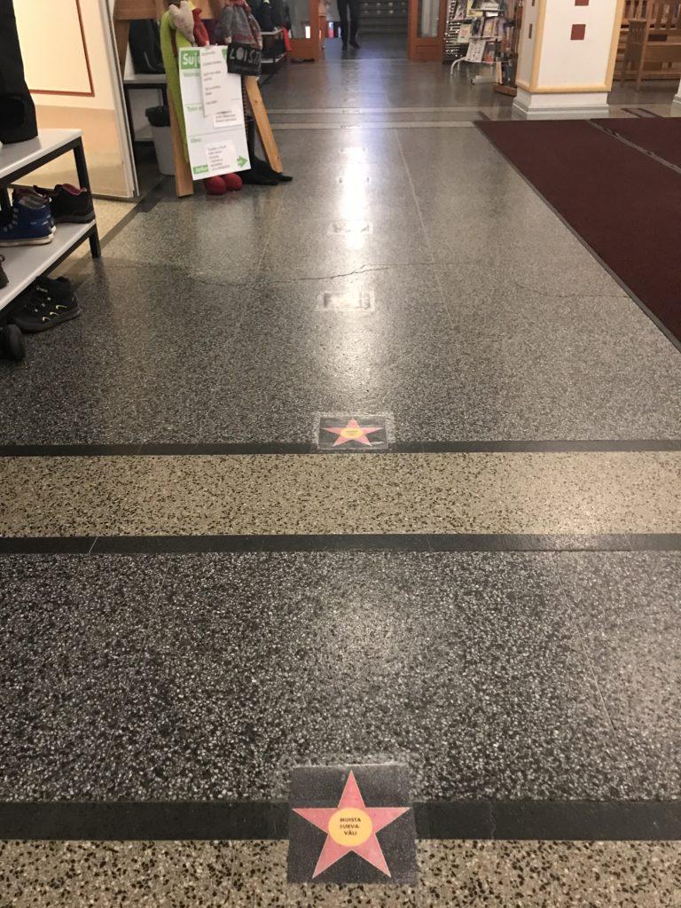 Välimatkoista muistuttavia tähtitarroja lattiassa koulussa.