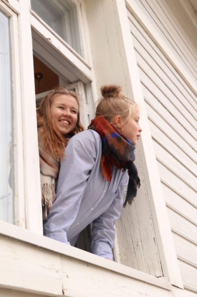 Kaksi teatterin nuorisolinjalaista nuorta naista ikkunalla, kuvattu ulkoa.